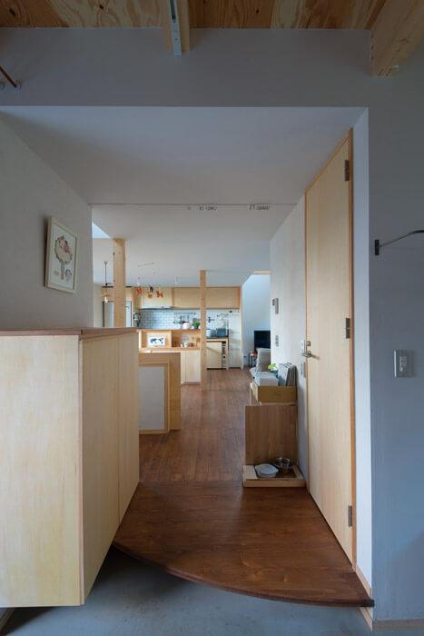 玄関から室内へはドアがなく、木の造作家具や建具のやわらかな印象の室内空間が広がる
