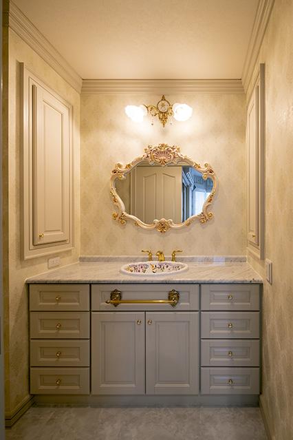 洗面室はユーテリティと分離。造作仕上げの洗面台に、奥さんが選んだアンティーク風の鏡と洗面ボウル、照明を組み合わせて