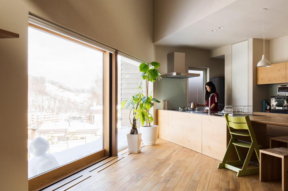 LDKの大きな掃き出し窓を木製サッシに。床や造作家具の色・質感に合わせることで、より統一感のある美しい住空間となっている