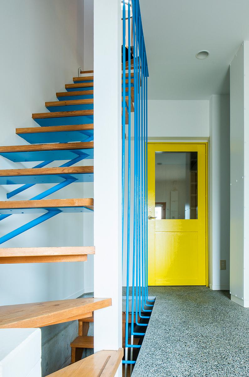 【AFTER】階段は鮮やかなブルーに染まり、居住スペースと隔てる部分にはイエローのドアが設置された