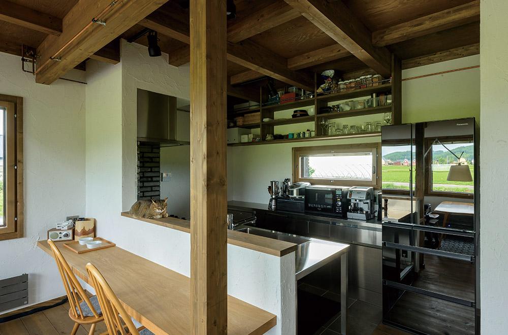 キッチンは、手入れのしやすいオールステンレス製のオーダーメイド。リビング側にはナラの一枚板で製作したカウンターを設置