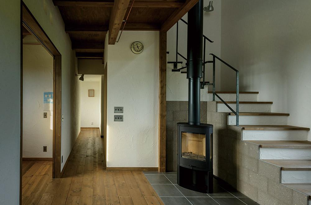 寒い季節も、薪ストーブで家全体が暖か。炉壁も兼ねる階段の側面は札幌軟石で仕上げ、ソフトな印象に