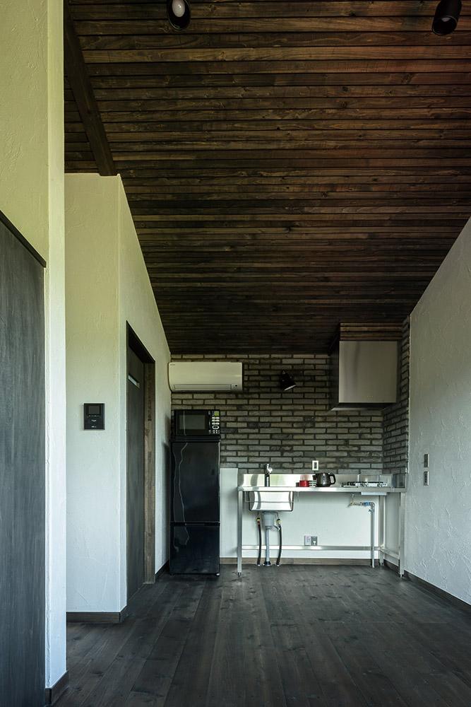 子世帯とは対照的にシックなトーンの内装。外壁と同じ横目透かし張りの緩やかな勾配天井と、グレー色のレンガ壁の組み合わせが、空間に心地よい変化をもたらしている