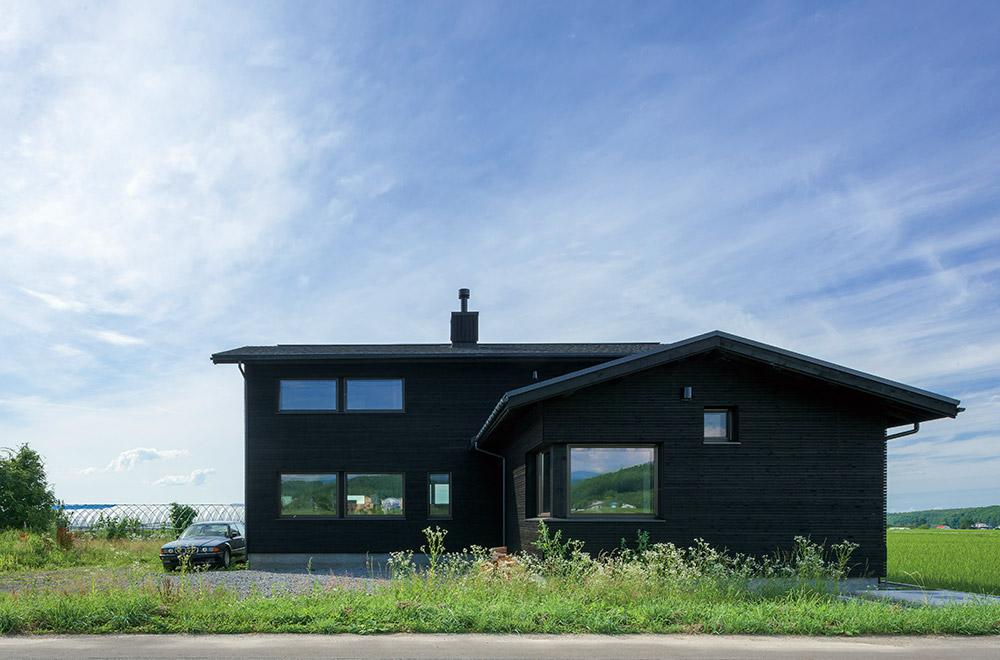 爽やかな風が渡る田園風景の中に建つYさんの住まいは、平屋と2階建てをL型に組み合わせた独立型の2世帯住宅