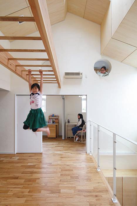 勾配天井と吹き抜けで開放感いっぱいの2階フリースペースをうんていが渡る。子ども部屋ロフトの丸窓が可愛らしい