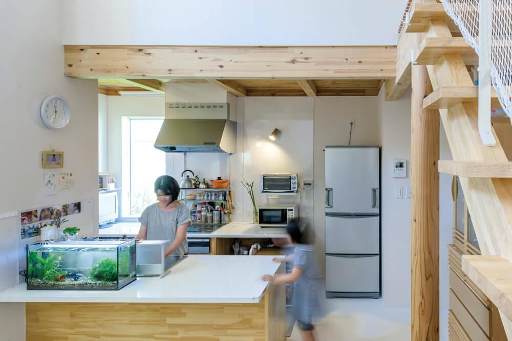 対面式キッチンはメラミン天板とステンレスシンクを用いた造作。天板はカウンターテーブルも兼ねる