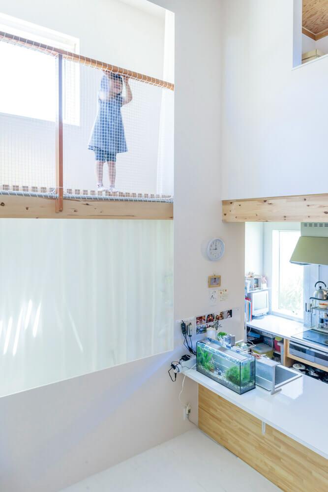 キッチンに隣接する1階のサンルームは半地下構造。物干しと収納を兼ね、目隠しのカーテンを設けた