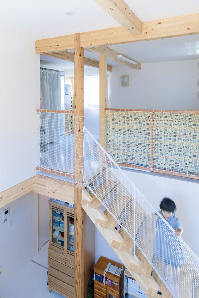 階段横に立つ親柱には、県産材のスギを使用。階段ホールの奥は寝室スペースになっており、お子さんの成長に合わせて間仕切り壁を設け、子ども部屋をつくる予定