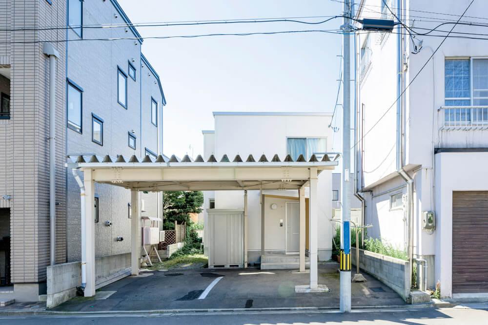 東西を3階建て住宅に囲まれたMさん宅。手前のカーポートは、既存のものを再活用。除雪の手間も軽減
