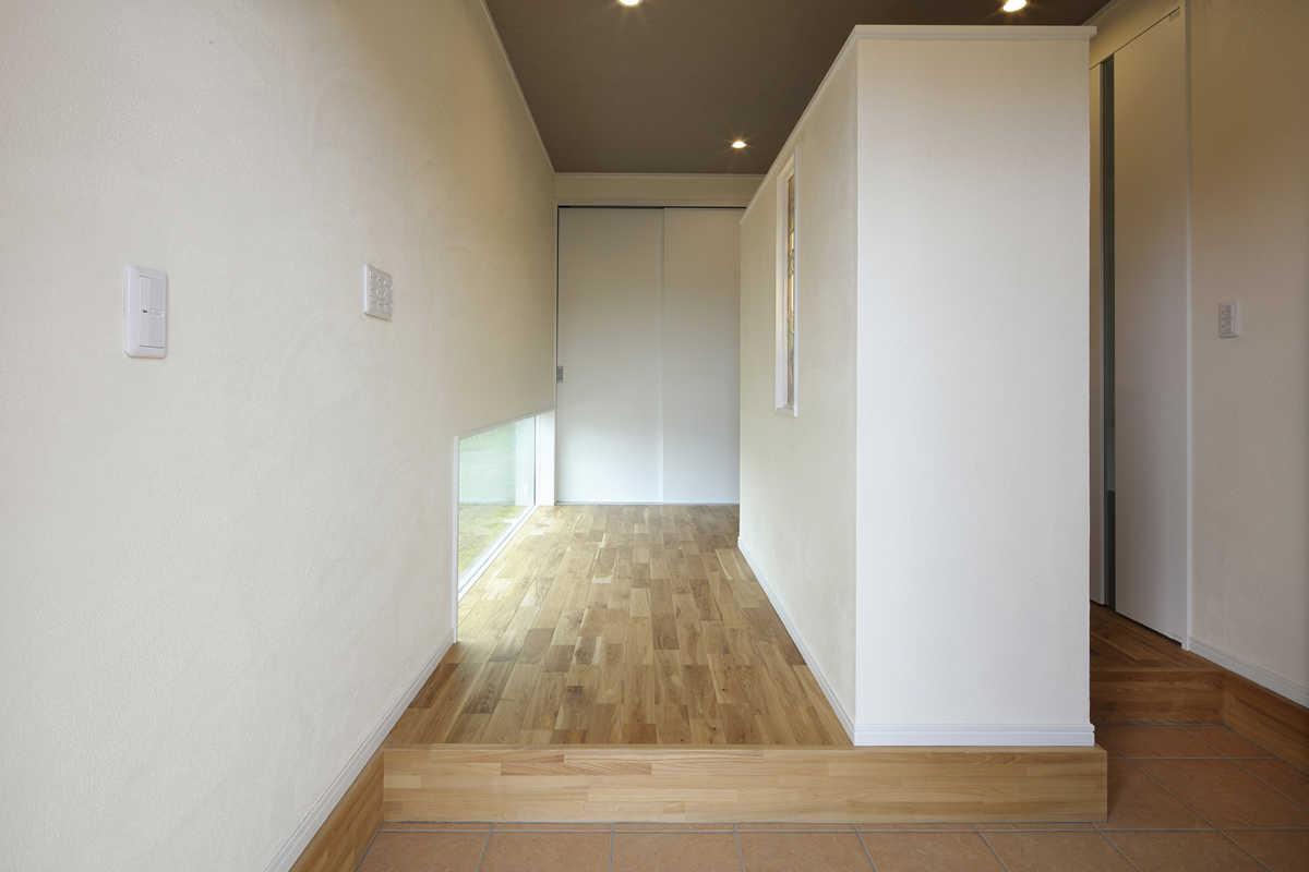 玄関ホール。正面と中央に収納スペース。右側シューズクローク側から入るとパントリーに直結する