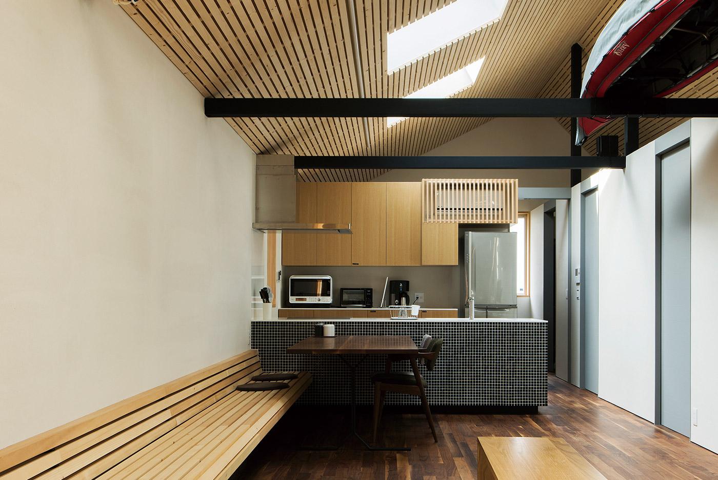 マツ材張りの天井と照明、造作ベンチが軽快なラインを描くLDK。天窓からこぼれる外光がつくる陰影も美しい