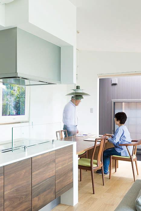 コンロ横や正面のガラスの仕切りが、視線は遮らずに食卓やリビング・スペースの落ち着きを確保する