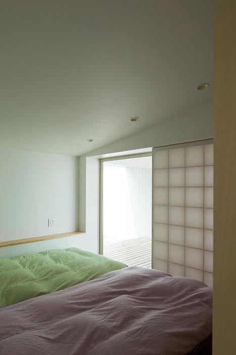 棚を造り付け、ベッドだけを置くシンプルな寝室。窓の外にはプライバシーを確保したデッキが続く