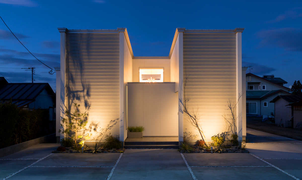 建物外観。夜には柔らかな照明が住まいを包む。変化のある植栽が動きのある影をつくる