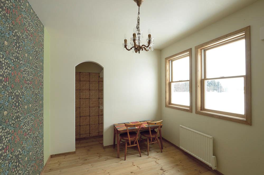 2階にある主寝室。壁の一面のみ、クラシカルなデザインで人気の「ウィリアム・モリス」壁紙を張り、空間のアクセントに。アールをつけた入口の先は、ウォークインクローゼット。2階には、このほかに子ども部屋2室とご主人のホビールームがある