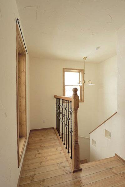 アイアンとパイン材で造作した手すり、パイン無垢のフローリング、木製サッシの開口で構成された階段ホール。素材感を生かしてシンプルにまとめた空間は、やさしい雰囲気に