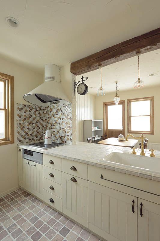 コブルストーンを床に敷きこんだ造作キッチンは、白を基調にまとめ、IHクッキングヒーターを採用。シンクには2年ほど経過すると侘びた雰囲気になる真鍮の水栓金具を取り付けた。最新の設備を導入しながら、こだわりのパーツを用いることで、時間が経つほどに味わいのある表情になる