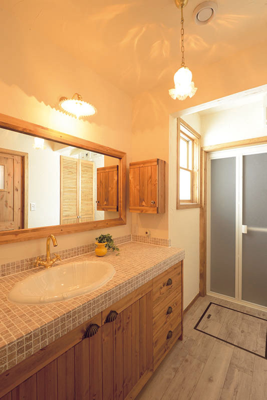 パインを面材や鏡フレームに用い、暖色のタイルで仕上げた造作洗面台。照明から扉の取っ手まで細部にわたってテイストを揃え、シンプルでありながら完成度の高いグルーミング空間に仕上げている
