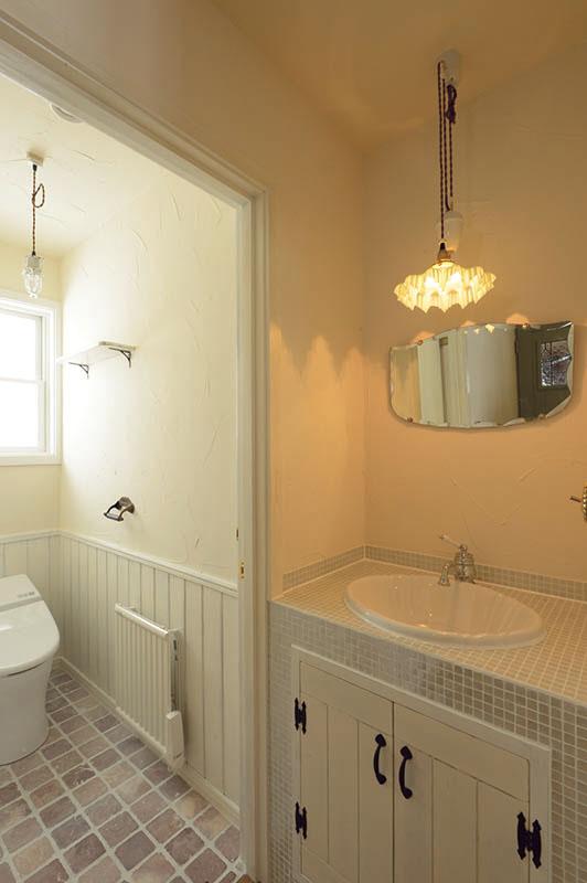 1階のリビング脇に設けたトイレ。手洗いスペースを独立させ、白を基調に造作した。鏡や照明、水栓金具などを吟味しつくり込むことで、小さなコーナーもインテリア性の高い空間に