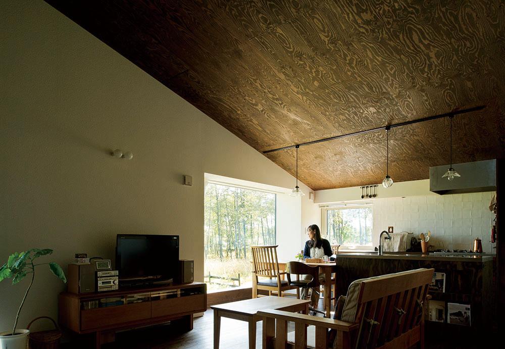 おおらかな勾配屋根に包まれるようなLDK。ダイニングの窓は大きく、外の白樺林が近くに感じられる。その他の窓はあえて控えめにし落ち着く空間に