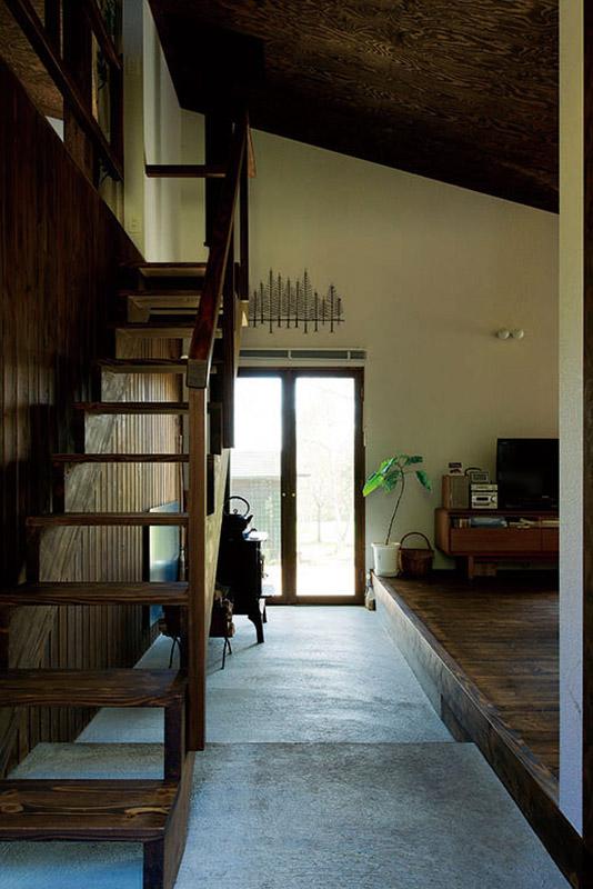 玄関からまっすぐに東側へと伸びる「通り土間」。その奥に薪ストーブが設置されている。家の中心となる土間は外と内のつながりを深めてくれる