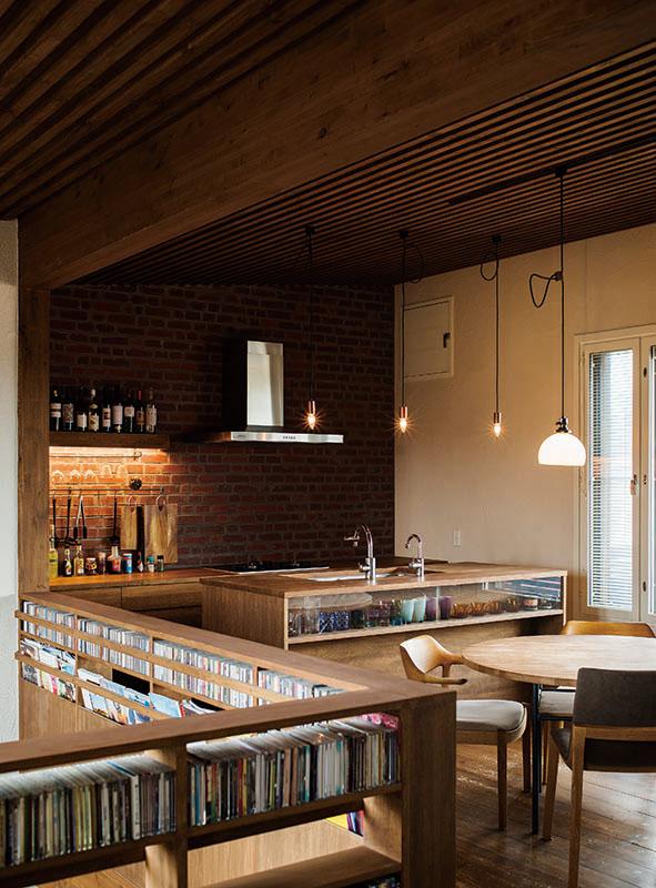 レンガの壁が目を引く造作キッチン。隣接して大容量のパントリーもある。ダイニングテーブルもスペースに合わせて高田さんがデザイン