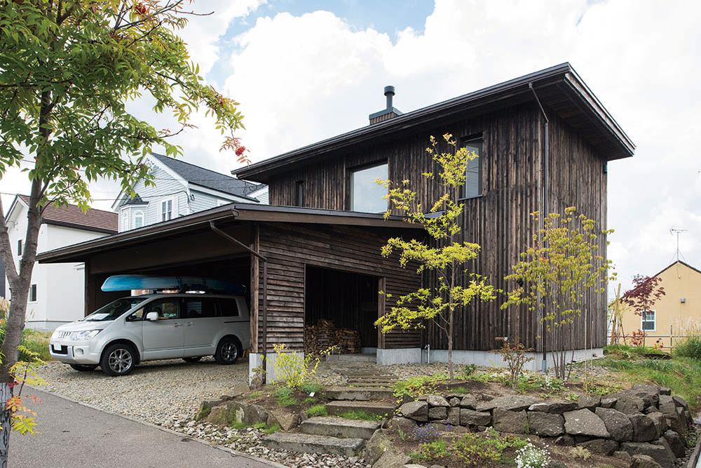 木酢液を浸透させた下川町産マツ材を大和張りにした外観。建物と一体化したカーポートは薪置場も兼ねる。アプローチの札幌軟石を使った前庭のデザインも建物に合わせて高田さんが手掛けた