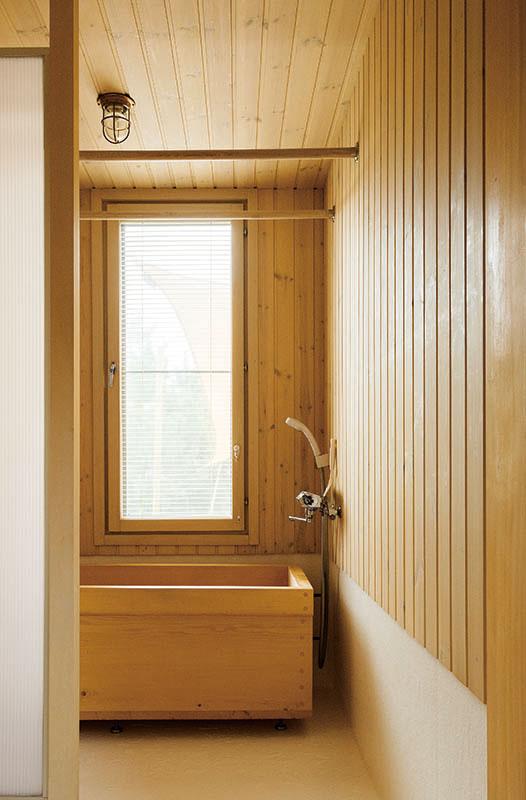 コウヤマキを用いた浴槽とヒバ羽目板の壁、FRP仕上げの床を採用した1階浴室。洗剤の飛び散りを防ぐシャワーブースを手前に設けて、メンテナンスがしやすいように配慮