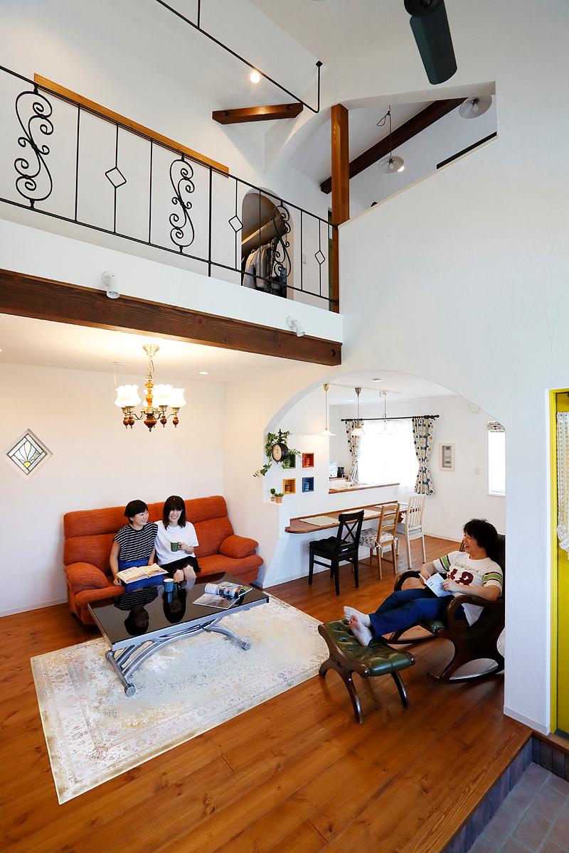 リビングでくつろぐご家族。白壁と木のシンプルなつくりにアイアンの黒や家具や建具、小物などの色がアクセントに