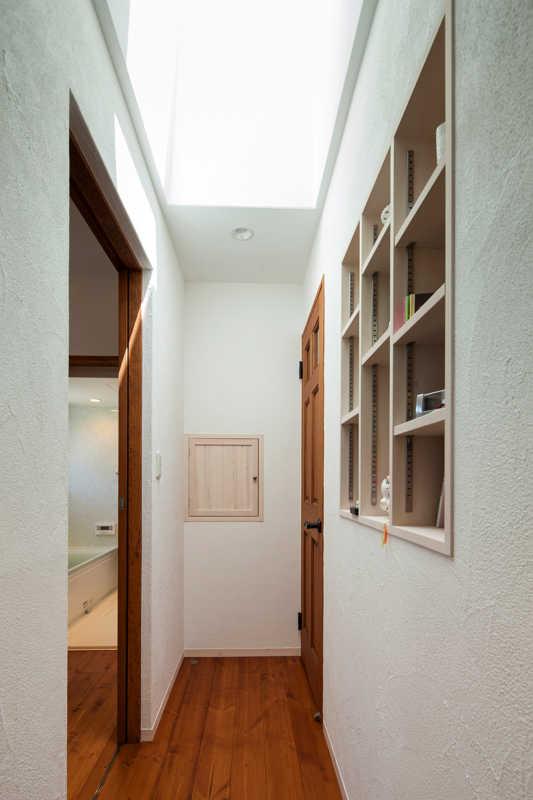 天窓から光が射し込む廊下。正面の扉はお父さんが休んでいるときでも洗濯物のやりとりなどができるように設けた