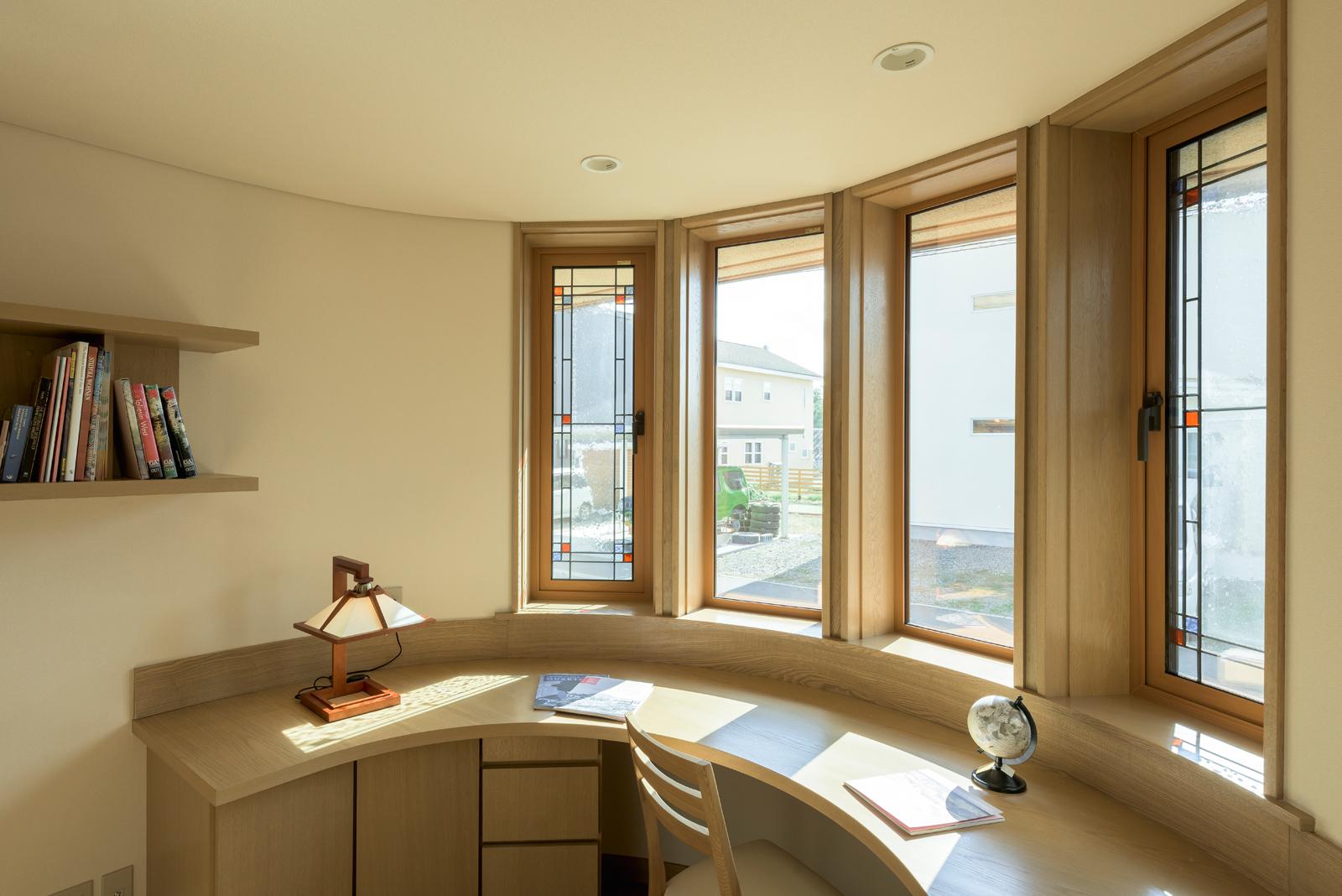 ファサードのポイントにもなっている優美なアールの内側は、書斎。その曲線に添うように、両サイドにステンドグラスを配した連続窓をしつらえ、デスクを造作した