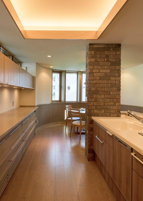 リビングと一体化させたキッチン。レンガやナラの質感を生かした仕上げを施し、採光窓や間接照明を採用することで、インテリア性を高めた