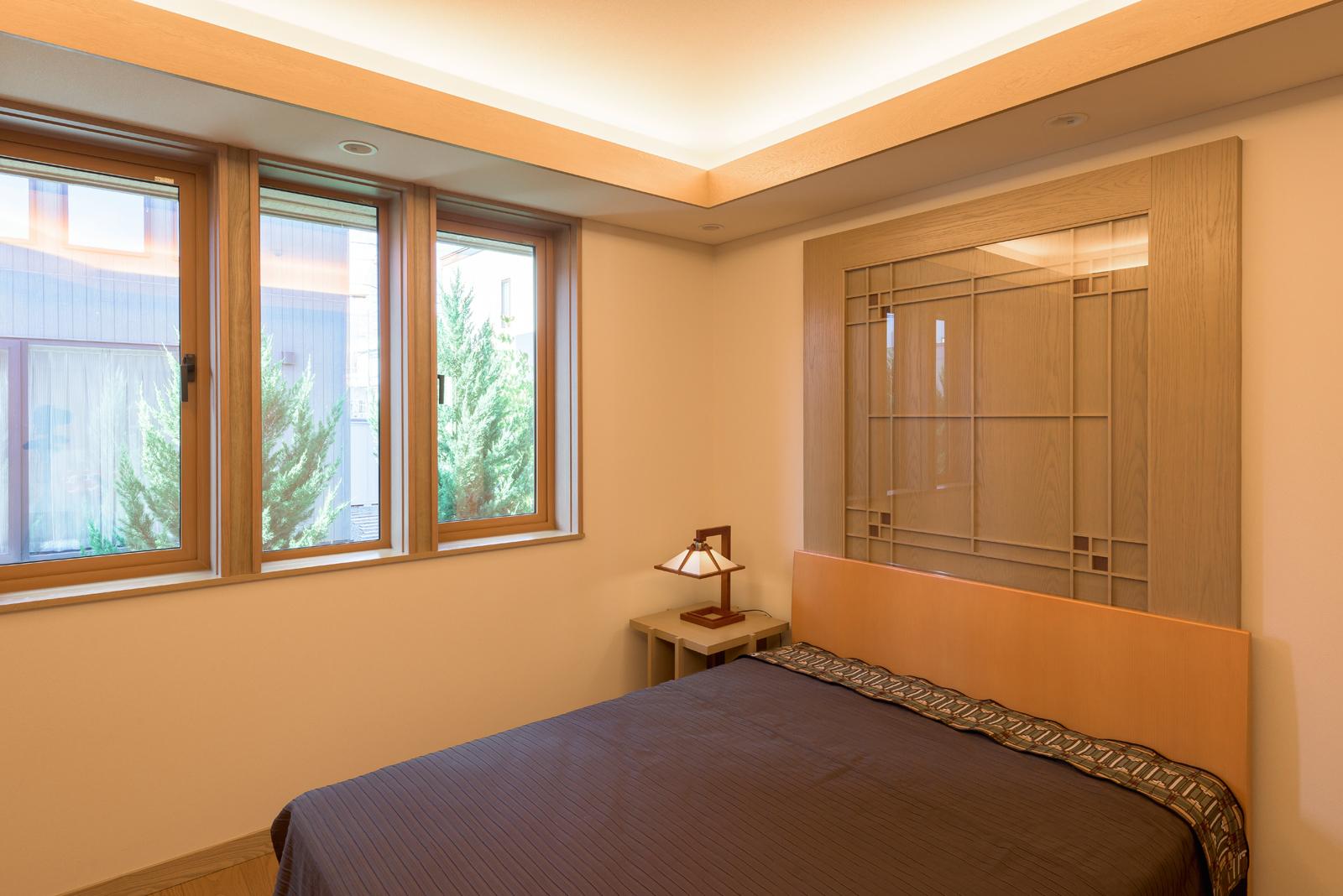 庭の緑や光を採り込む開口を設けた主寝室は、アイ建築工房でデザインを起こしたヘッドボードをシンプルな空間のアクセントに