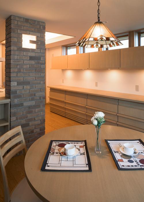 ライトの意匠にマッチするステンドグラスのペンダントを採用したダイニング。キッチンとの間仕切りレンガ壁にも、間接照明を設置