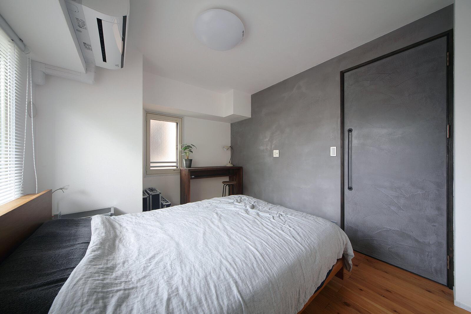 ベッドルームのグレーの壁には日本製のセメント系左官材を採用し、モルタルの風合いを生み出した