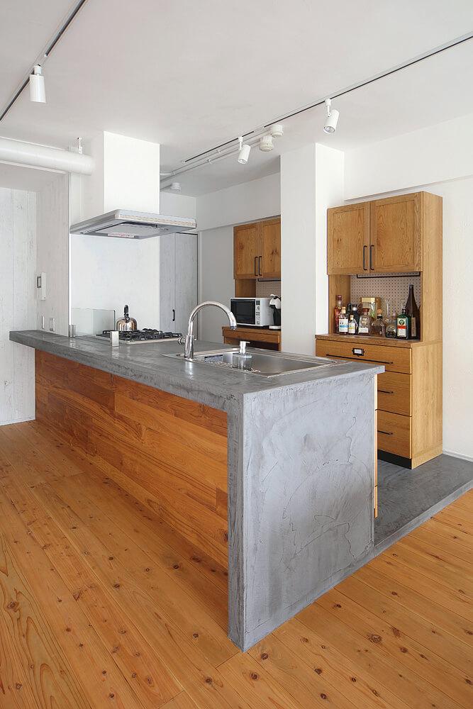 ワークトップに水まわりに強い左官材を塗り、前面にはブラックチークウッドパネルを施工。既製品のキッチンがオリジナル仕様に