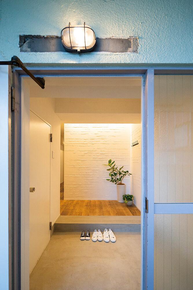 モルタル造形で仕上げた壁面が印象的な玄関。古めかしさの残る扉まわりとも調和している