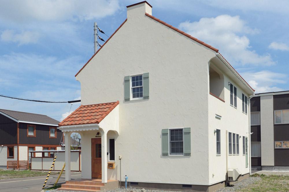 陶板瓦の三角屋根、アンティーク風の窓やポーチがシンプルなフォルムに「大人かわいい」アクセントを与えている、Kさん宅の外観