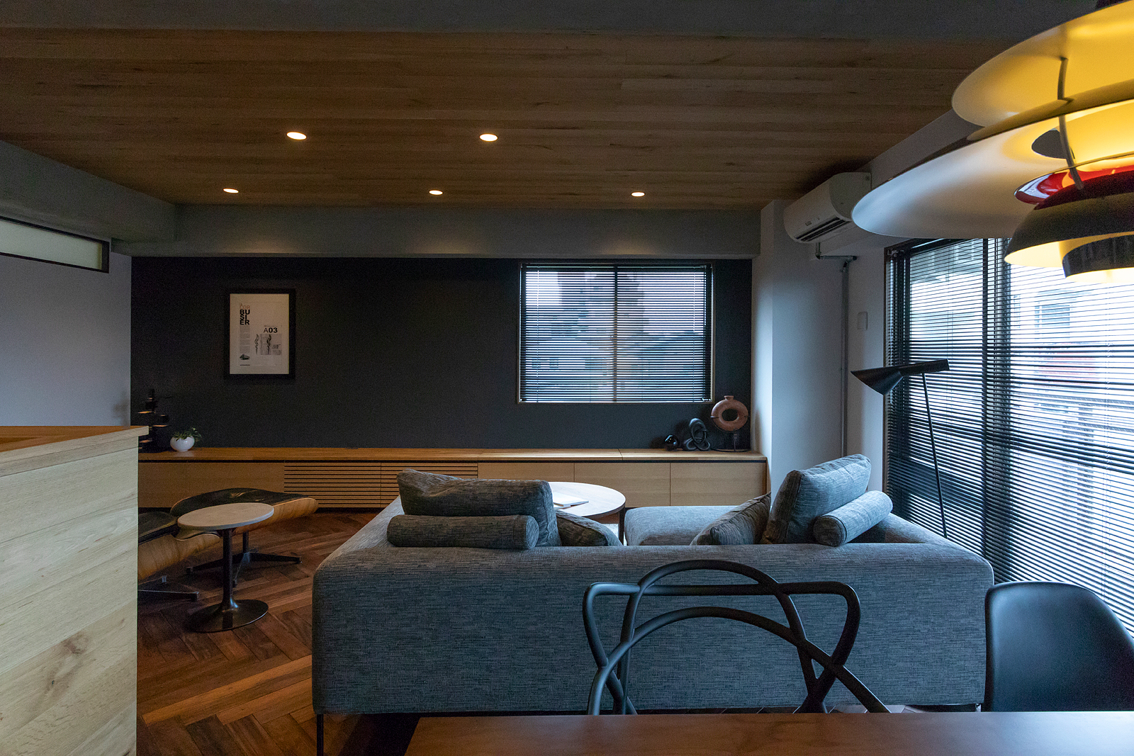 天井や床の木の質感が居心地の良さを引き立てる。奥のグレーの壁は窯業系サイディングでマットな質感を演出
