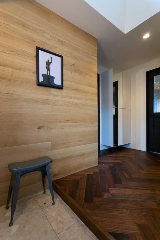 木を張って上質感を高めた玄関。床にはLDKと同様、こだわりのウォールナット・ヘリンボーンを敷き詰めた