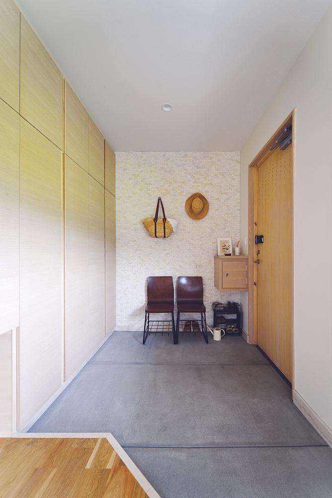 壁に大理石のタイルを張った土間玄関。タモ材の突板を使ったシューズクローゼットは、容量もたっぷり