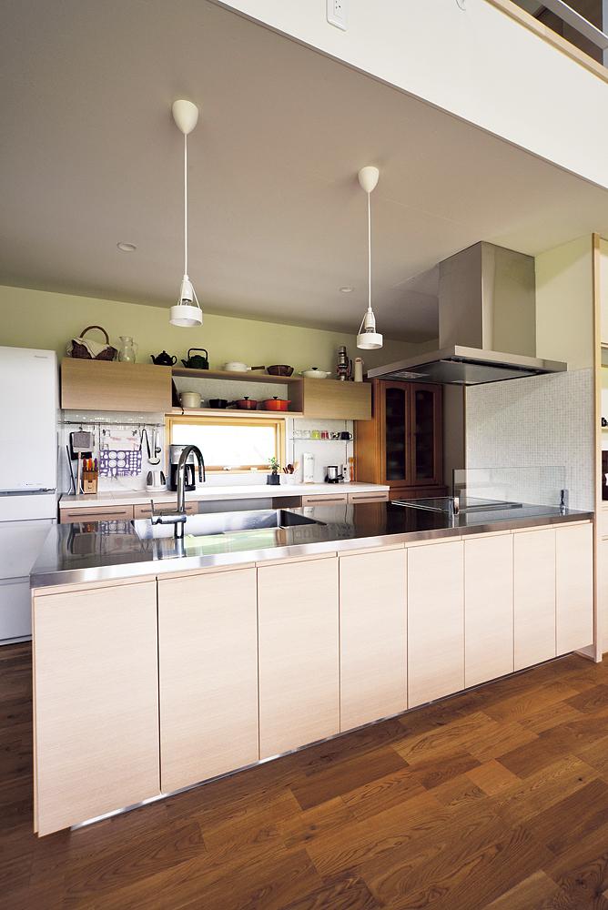 タモの面材とステンレスの天板を採用した対面キッチン。背面にはライムストーンと大理石タイルを効果的に配した収納カウンターを設置。造作ならではの美しさと実用性を兼ね備えたキッチンは奥さんのお気に入り