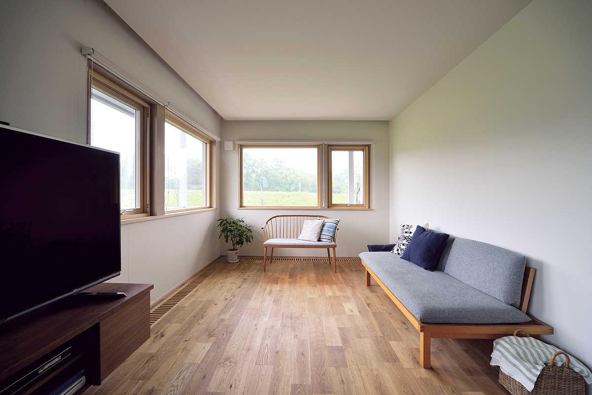 L字に配した開口から、河畔林の緑が染み込むようなリビング。東川の家具工房に特注したウォールナットのダイニングテーブルと素材を合わせ、TV台と吹き抜けの間接照明もデザインし、造作した。シックな木の色が白を基調にした開放的な空間を引き締める