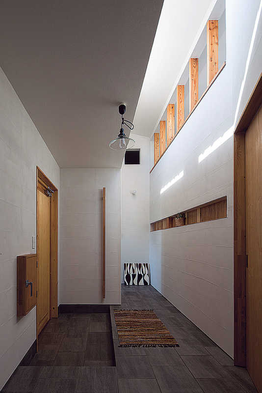 ハイサイドライトからの光をLDK側にも取り込めるスケルトンの開口がある玄関ホールは、タイル仕上げの床に床暖を設けて冬も暖か