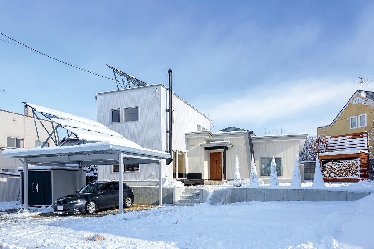 建物は、白を基調にシンプルですっきりとまとめて。カーポートと建物の屋根には7.8kWの太陽光パネルが搭載されている