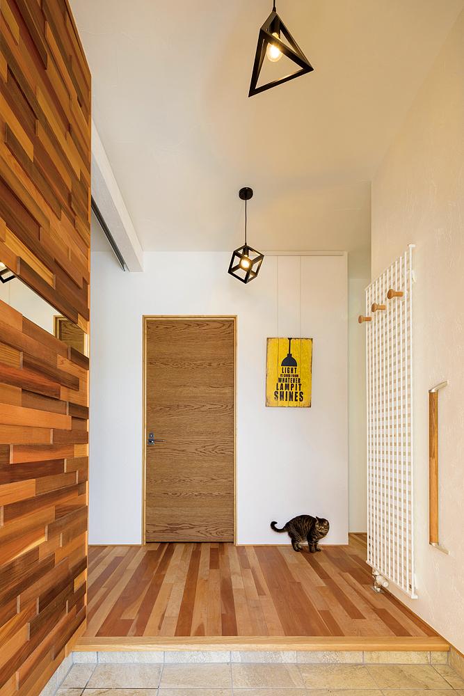 アサダ無垢床とレッドシダーのデザインウォールが印象的な玄関ホール。デザインウォールは、大工さんの力作