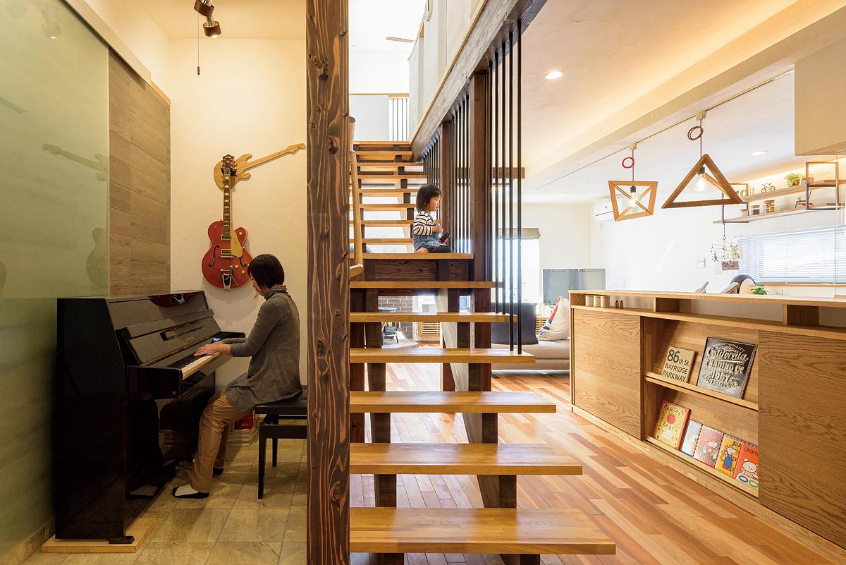 アイアンとナラを組み合わせた力桁型の造作階段の横は土間床にし、小さなピアノスペースを設けた