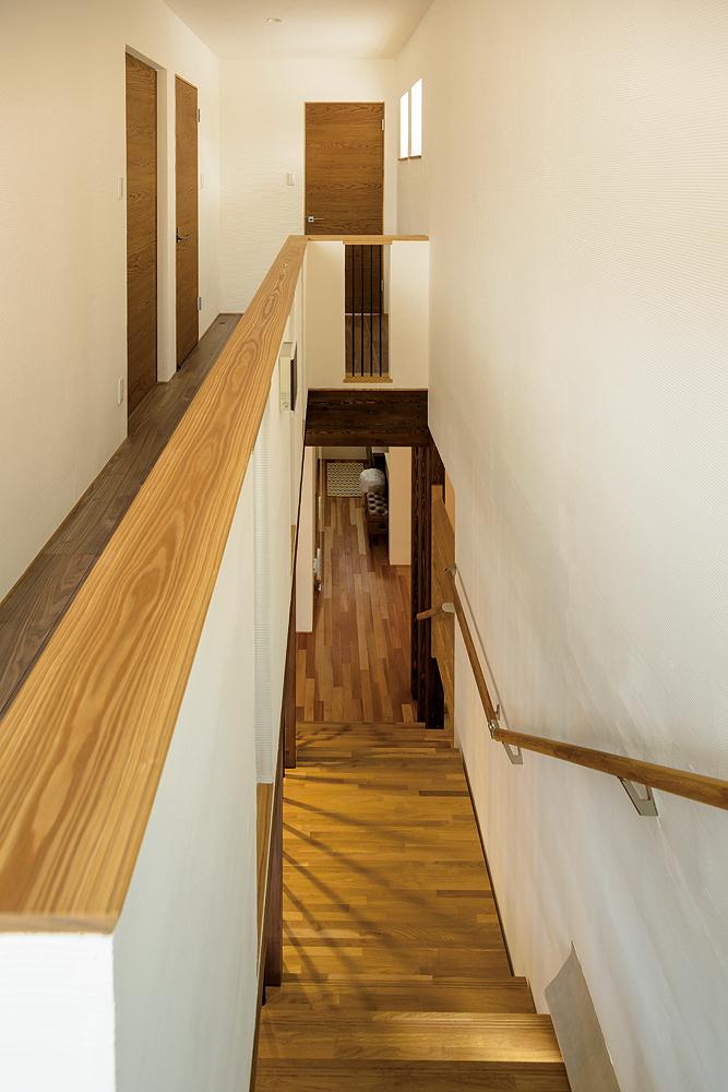 櫛引仕上げの塗り壁とナラの床板、アイアン柵が美しい調和を見せる階段。正面は子ども室