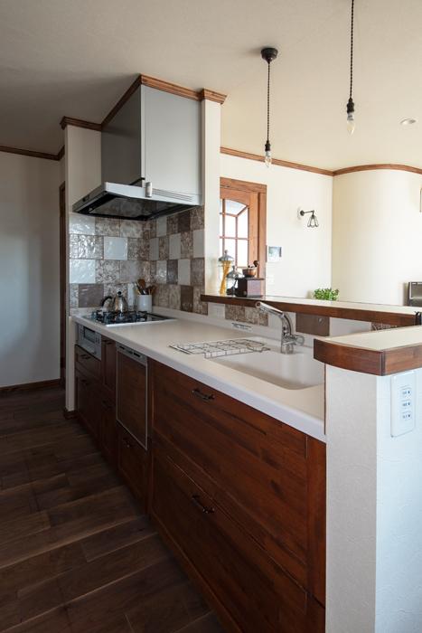使い勝手のいいキッチンには、ペルーの住宅によく用いられているスペイン風のタイルを採用し、背面の造作収納と合わせて面材をつくり変えた
