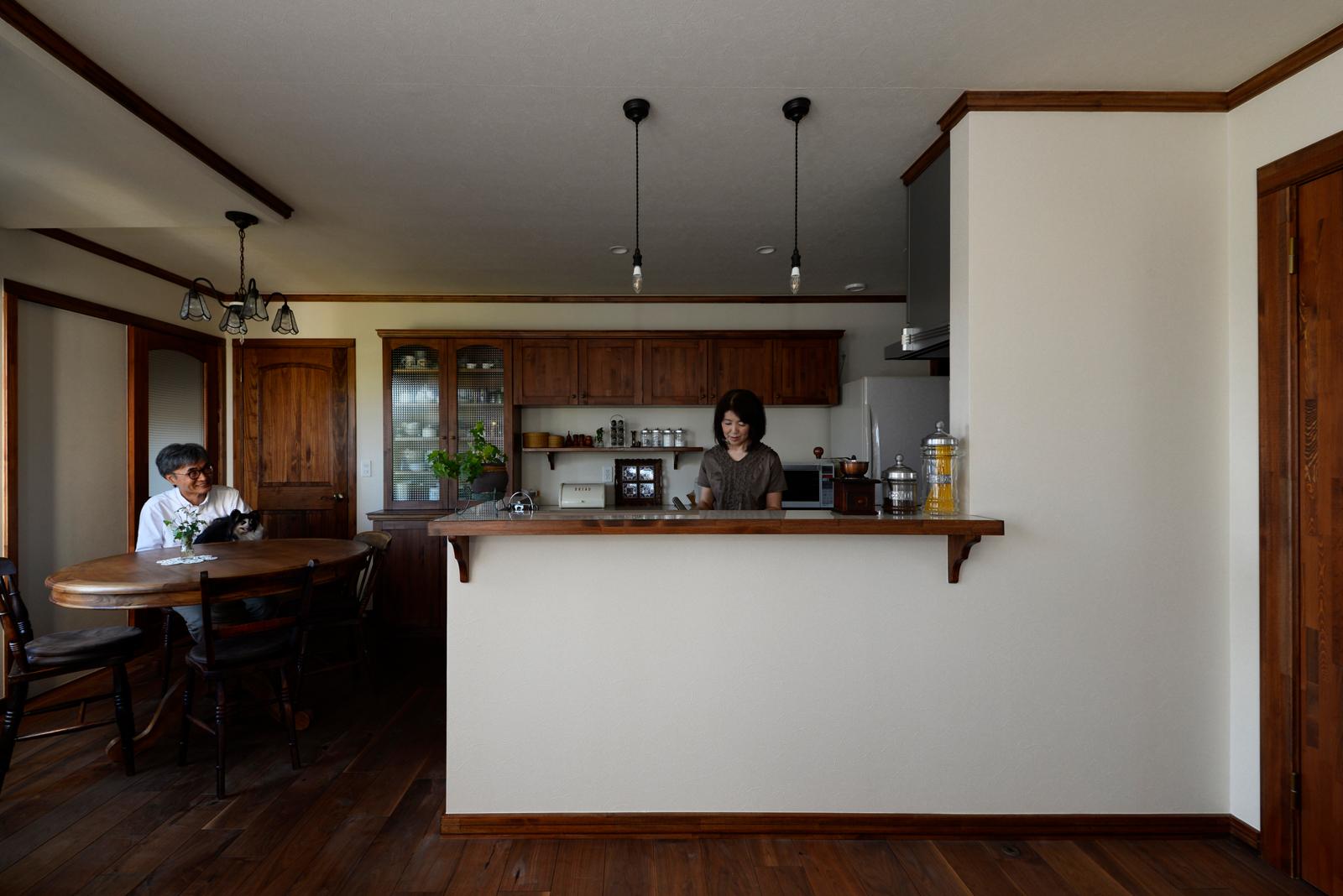 ダークブラウンを基調とした対面キッチンは、造作仕様。親世帯の床はすべて、ウォールナットの無垢材で統一して落ち着きのある空間に